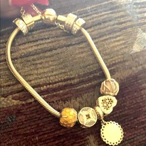 Gold pandora bracelet with 7 gold charms included